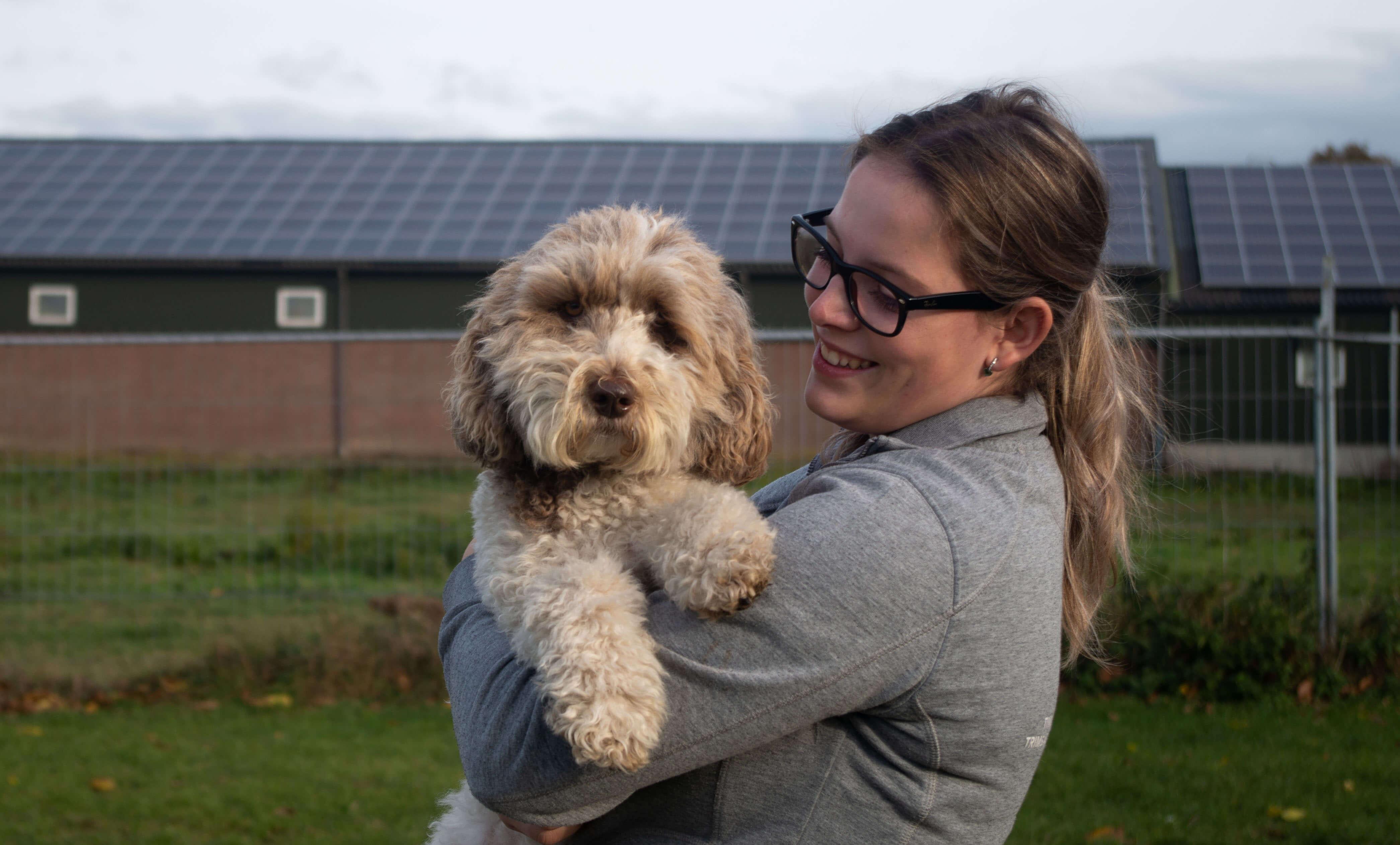 Vrouw die een hondje vast heeft.